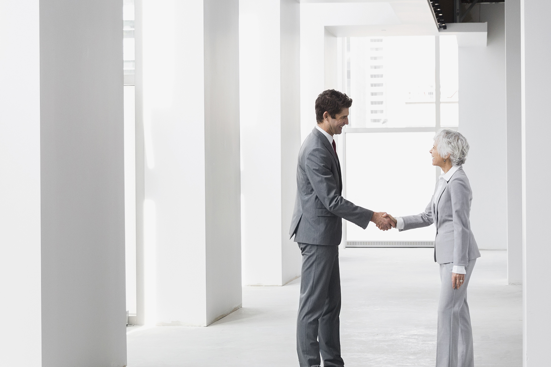 Businessman and businesswoman handshaking in empty office