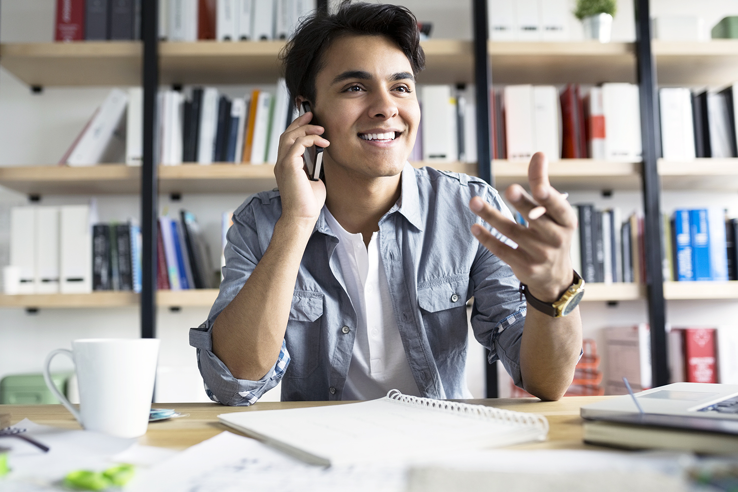 Young businessman talking on cell phone in office