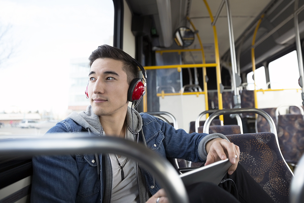 Pensive young man riding bus listening music headphones