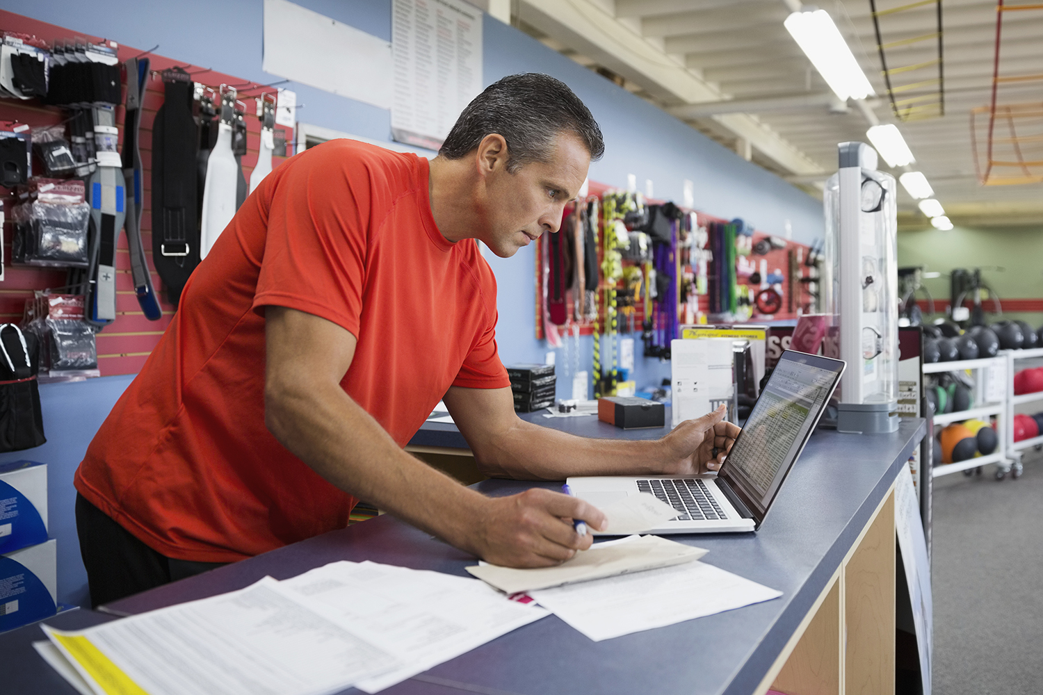 Business owner working at laptop at counter in home gym equipment store