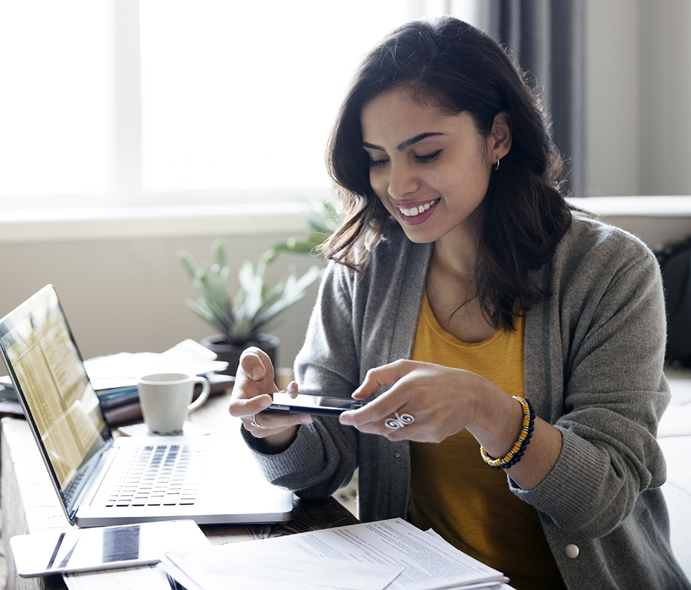 Young woman depositing check online with camera phone in living room