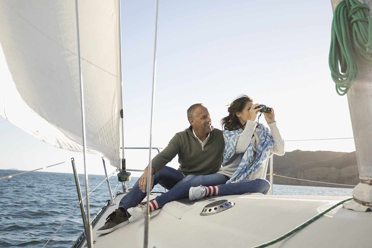 Mature couple using camera on sunny sailboat
