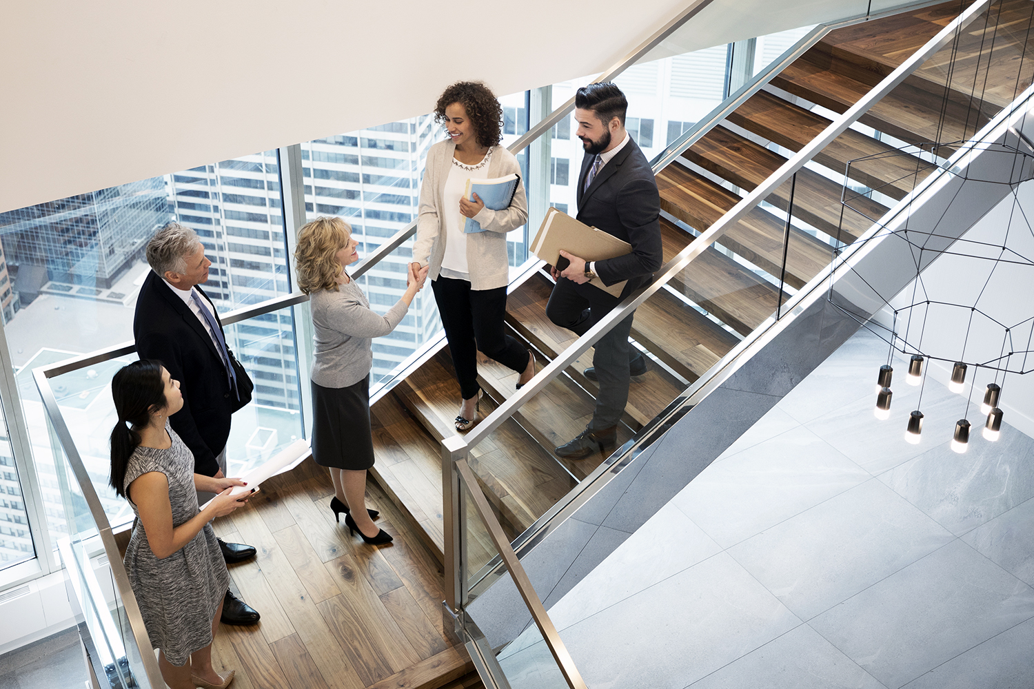 Business people handshaking on modern, urban office staircase