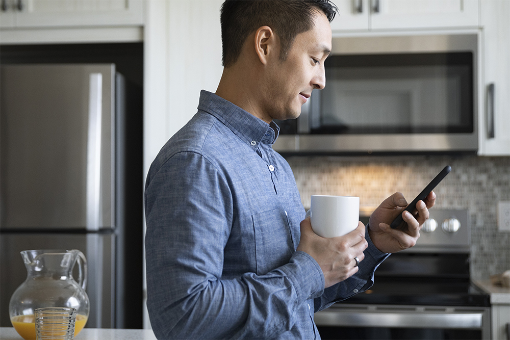 Man drinking coffee and using smart phone in morning kitchen