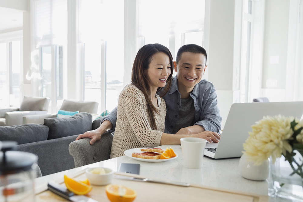 Couple at laptop in kitchen at breakfast