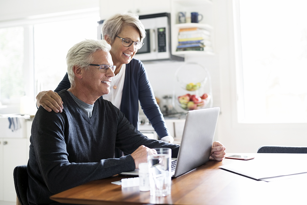 Senior couple using laptop at kitchen table