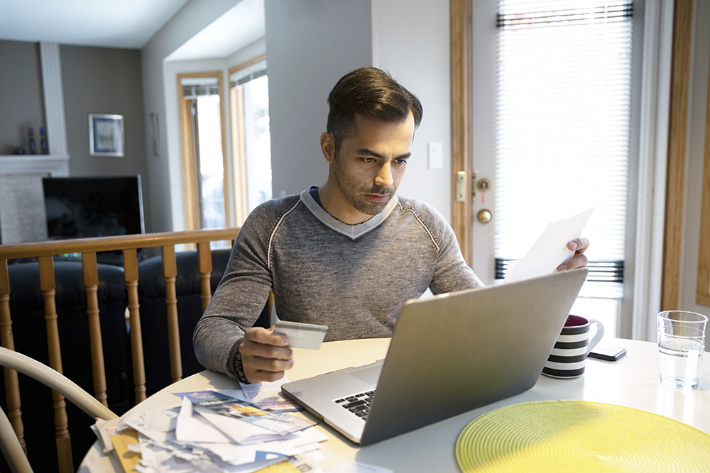 A man with credit card paying bills at laptop