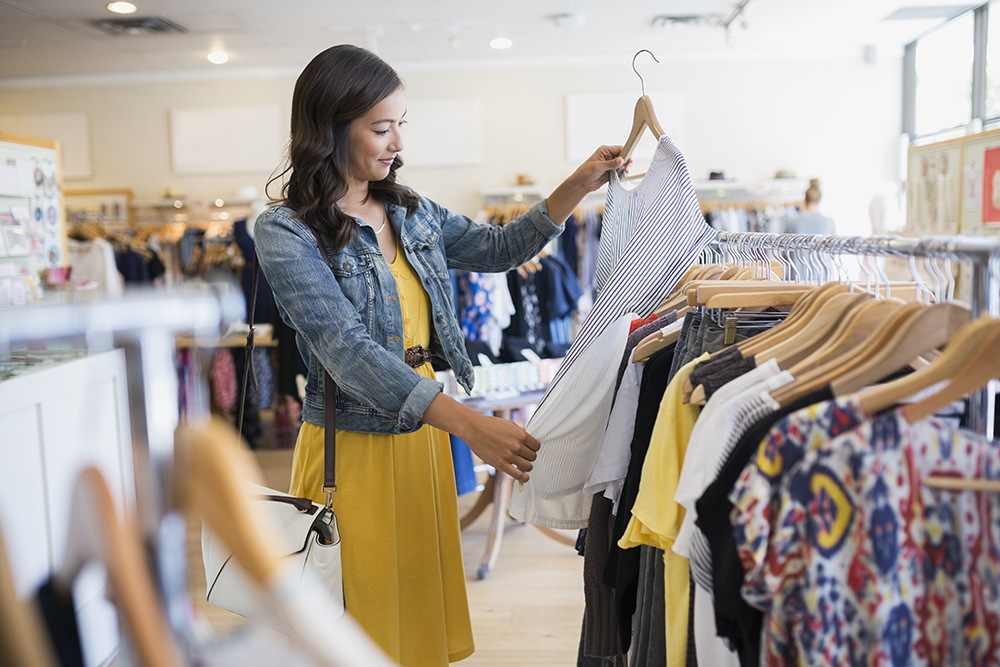 Woman eyeing shirt in clothing shop