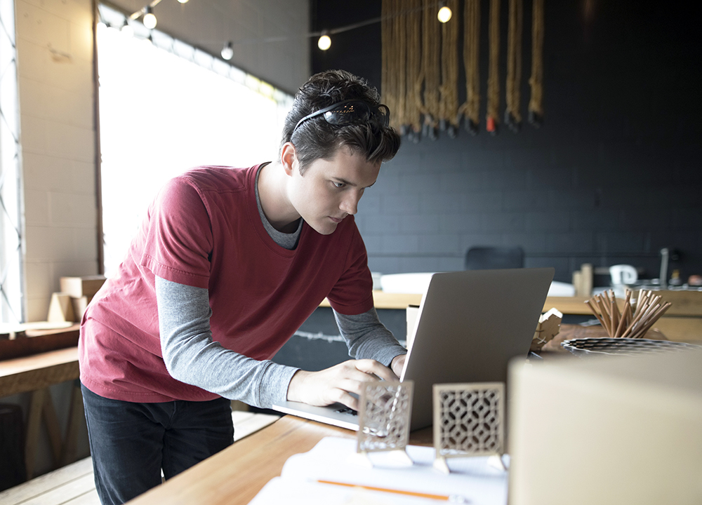 Focused male designer working at laptop in workshop