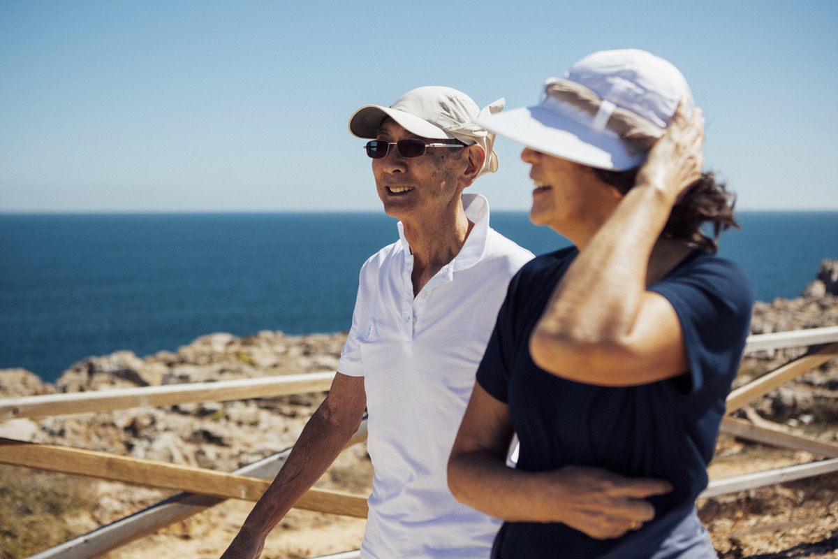Smiling senior couple looking at sea while standing by railing against clear sky