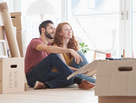 Young couple in new flat with cardboard boxes